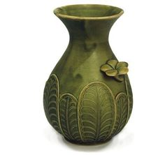 Green Flowered Ceramic Vase by 7 Loaves. $22.95. This exotic Balinese vase with leaf motif makes a subtle statement with its natural moss green glaze finish. The three dimensional floral accents have been applied by hand and bring the outdoors inside.  Add a cutting of your favorite rose bush to this unique vase and say, I care about the details. Create a set to complete the room.