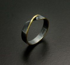 Fine gold foil is Keum Booed on the edge of the silver ring. The ring is a band twisted 180° once so its a Möbius loop. The silver is patinaed to