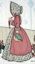 """#10 """"Bonnet Girl Relatives & Friends""""  Laura $6.50. Laura is holding a basket full of freshly baked bread covered with a napkin. Appliqué flowers are along the fence. Her hair is made from embroidery floss covered by her pioneer style bonnet."""