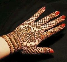 Henna or mehndi designs on hand. Red manicure.