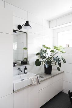 vitt badrum med svart golv, stort kakel badrum, monstrera