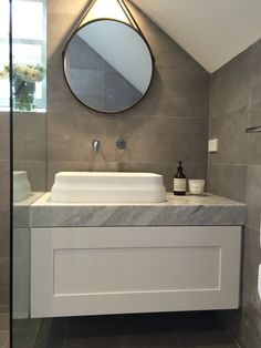 Ensuite bathroom. Grey and white. Carrara marble vanity. Omvivo basin. Omvivo spout. Round mirror. Sloping ceiling. Shaker style draw.