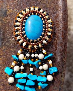 Southwest Sunset ~ Fringed Turquoise Brooch by The Alluring Bead Boutique The turquoise gemstone Cabochon and nuggets steal the show on this brooch. But the Beige Picasso CzechMate Superduos and the Ivory rounds in the fringe are the perfect contrast.