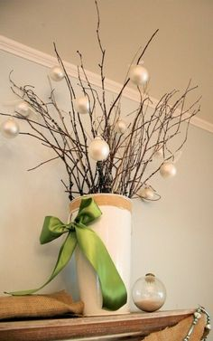 Grab branches from outdoors now that the leaves have fallen...arrange in vase to dry out,  put aside to create this elegantly easy holiday decor. Would use colored ornaments!