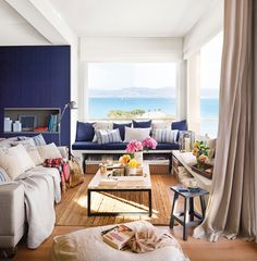 Salón con vistas al mar en blanco y azul con sofá, banco bajoventana y mesa de centro industrial 407813