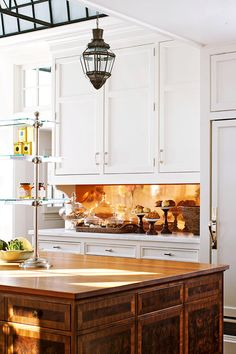 Joan designed the walnut island with its teak top. A polished copper backsplash reflects the light and complements the copper pans hanging above the range.