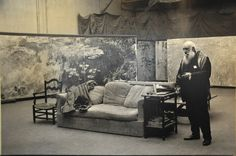 This is a view of Claude Monet standing in his first studio amidst his favorite canvases.