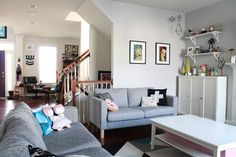 Love the dominant white with grey couches and colourful decor accents.