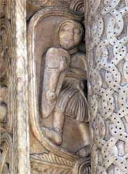 San Lorenzo a Genova. Molto interessanti sono i rilievi scolpiti sulla parte esterna del piedritto, purtroppo in parte coperti dalla colonna. Un soldato, un cavalire, l'asino che suona l'arpa...