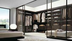 wood-paneled walk-in closet divided by transparent mirror wall from bedside