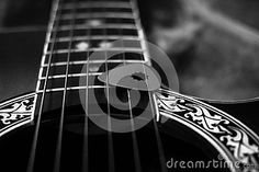 Close up view of a guitar with decorative details and pick, in black and white.