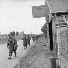 WW2 - Allies - British Infantry: Troops passing Café Gondrée at Bénouville, near 'Pegasus Bridge' over the Caen Canal, 9 June 1944.