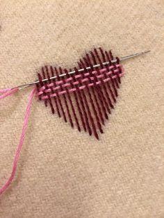 Gewebtes Herz. Süße Idee für dekorative Stickerei und Verzierung auf Pullovern. Kreative Stickerei zum Stopfen von kleinen Löchern.