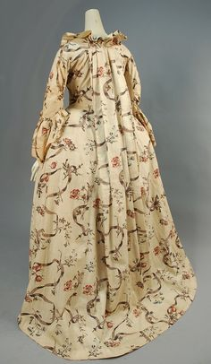 Rear view, robe à la francaise and matching mitts, France, 1750-1770. Cream printed with brown meandering ribbons and polychrome floral sprays, open gown having elbow length sleeve with scalloped fan cuff, ruffled neckline and front with stomacher panel, skirt front trimmed with self bows, unlined.