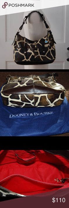 """Dooney & Bourke Medium Giraffe Print Safari Hobo Pre-loved, beautifully cared for hobo shoulder bag. Giraffe print with gold tone metal hardware; brand embossed metal placard on front. Adjustable shoulder strap (9"""" drop) with buckles; zipper closure; two outside front pockets w/ tab-snap closure; zip pocket on back. Red fabric lining w/ inside zip and slot pockets, and clip leash. Comes with blue Dooney & Bourke storage bag, original tags and product brochure. No marks or stains. From a…"""