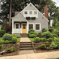 grey exterior home, yellow front door. charming