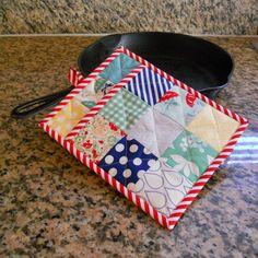Patchwork Pot Holder-by Hillary Smith- I love working with pre-cuts and this is a simple and quick project that uses the adorable Moda Mini Charm Packs. There are enough mini charms in a pack to make 3 pot holders, but you'll need more of your other materials.