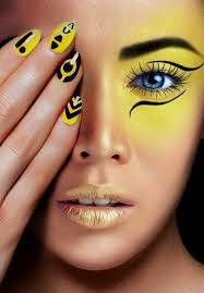 Yellow and black tribal style makeup and finger nail art.