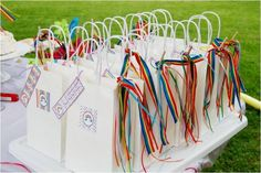 I really like the idea of doing gift bags to say thank you to your guests for coming. The rainbow ribbon really ties into the theme