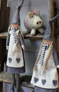 Dos muñequitas, de delantal blanco con corazón