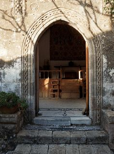 The arched doorway to the main house features a braided-rope motif typical of kapetani houses. Jasper Conran's retreat on the island of Rhodes