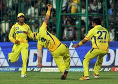 Chennai Super Kings fielder Suresh Raina (C) celebrates the wicket of Mumbai Indians batsman Harbhajan Singh with his teammate during the IPL Twenty20 cricket 2nd Playoff match between Chennai Super Kings and Mumbai Indians at the M. Chinnaswamy Stadium in Bangalore on May 23, 2012.