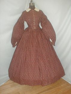 "1860s cotton print dress, terra cotta, white & teal blue on brown background; bodice lined in cotton & has front button closure, piping at neck, armscyes & waist; skirt unlined, cartridge pleated, light underarm discoloration; embroidered collar original to dress; bust: 34""; waist: 28""; skirt length: 41""; hem width: 180:"