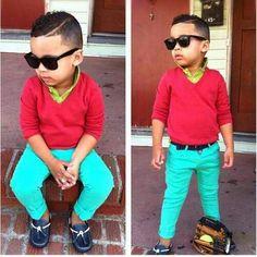 El chico lleva un sueter rojos, los pantalones azules, y los zapatos azules.