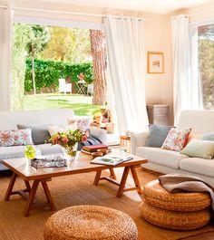 Salón con chimenea, cortinas blancas, alfombra y puffs de fibras, mesa de centro de madera y lámpara de pie