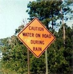 Caution: Water on road during rain sign.