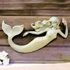 Sea Beauty Mermaid Wall Sculpture. Painted polyresin mermaid figurine carved to look like wood mounts to any flat surface. Built-in mounting.