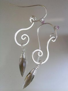 """18 gauge argentium silver wire lengths have been forged into small curvy scrolls and tipped with elongated smoky quartz briolettes (17mm)    Hand fabricated 20 gauge argentium silver ear hooks are uniquely adorned with lilac sapphire rondelles.    Entire length is a shot over 2 1/2"""". Width is under 1/2""""."""