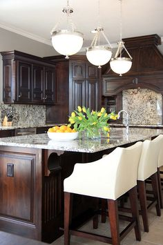 How to change your dark-stained kitchen cabinets without painting them. The designer updated this kitchen by only changing the old counters and backsplash for granite. This is a good idea if you're trying to sell your home and do a quick kitchen reno before putting it on the market.#darkstainedcabinet #kitchenreno Bria Hammel Interiors