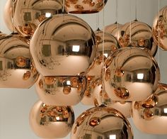 A pendant light by Tom Dixon made using copper, a material more commonly associated with solar cells and microwave radiation. The Copper Shade is created by exploding a thin layer of pure metal onto the internal surface of a polycarbonate globe. The result is a highly reflective surface with a warm metallic glow. Extremely small holes can appear at times within the metal coating due to environmental conditions. Also available in 25cm size.