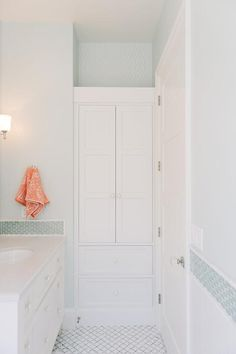 Chic cottage kid's bathroom features light blue paint on the walls accented with blue glass oval border tiles lined with a white footed single vanity next to a built-in linen cabinet painted white, Benjamin Moore White Dove, alongside a white and gray marble tile floor.