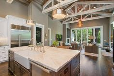 A large, elegant island opens up to the family room, and a rustic farm table in front of the island serves as a cozy spot for family dining and entertaining. As reclaimed 100-year old barn wood adorns the ceiling, large white trestles add texture and beauty, while anchoring the entire space.