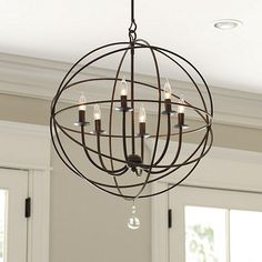 Ballard Designs Orb Chandelier Item: LC628 $399.00 - $499.00 This impressive chandelier features an openwork sphere of hand wrought iron surrounding six upright globe lights to illuminate your space. A single clear glass ball finial drops from the center for sparkling punctuation. Adds a lot of look in a dining room, living room or entry.