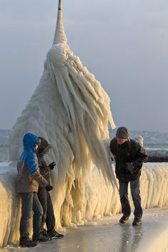In this photo Tuesday, Feb. 7, 2012 photo people stand next to a natural ice sculpture that was formed after the wind blew waves over the boardwalk of Lake Geneva at the Port of Choiseul in Versoix near Geneva, Switzerland. A cold spell has reached Europe with temperatures plummeting far below zero. (AP Photo/Keystone, Salvatore Di Nolfi)