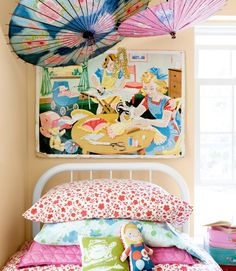 Antique paper parasols decorate the walls in this girl's room. The old iron bed frame is a $15 tag-sale steal, spiffed up with a fresh coat of paint. The linens are from eBay and Goodwill; the owner of this Maine home designed the frog pillow herself. A 1950s home-ec poster, scored at a vintage shop, hangs in the corner.   - CountryLiving.com