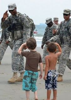 Hey look!, these small boys know how to salute the troops. But our so called President doesn't.
