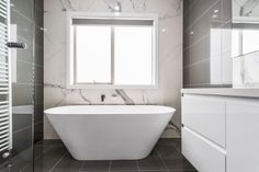 The large, trapezoidal bathtub reflects the light let in through the perfectly aligned bathroom, brightening the entire room, despite the floor to ceiling grey tiling. Tiling, Cabinet Design, Melbourne, Cabinets, Custom Design, New Homes, Bathtub, Interiors, Flooring