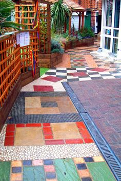 More Pins Like This At FOSTERGINGER @ PinterestAnother example of a mosaic pathway but in a more regular arrangement and more 'traditional'. I like the use of neutral colours being offset by more vibrant blues and reds and greens. You could use this as a path or perhaps a border around flowers beds and trees. A patio could even be created out of it. For children the variety arrangement of the tiles and colour would make this a very sensory place