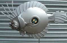 """Ptolemy Elrington is 43-year-old artist from United Kingdom who use old hubcaps to make dogs, fishes, birds, dragon and other sculptures with knife and hacksaw. Artist said: """"I like to work with reclaimed materials to show that what is one person's junk is another man's treasure"""". He likes to use BMW and Mercedes caps because of their quality and flexibility."""