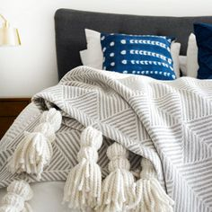 Save money and add giant tassels to a plain throw blanket for a super cozy look in your bedroom!