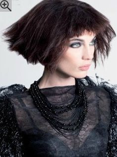 Short bob with raised sides and a very short fringe. The hair is teased for volume.