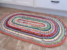 This is my signature style of crocheted rag rug- I use every color of the rainbow to make it and it matches any decor or color scheme. This rug will add a pop of color in front of a kitchen sink (or anywhere in your house!) and provide a soft cushion underfoot.  I spend about 2-3 weeks creating each rug- from choosing the color scheme, to cutting the recycled fabric into strips, to joining them together into one continuous strand, and then crocheting the fabric yarn into a unique work of…