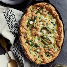 This terrific baked omelet recipe combines just-cooked asparagus and sautéed peas and zucchini with crumbled goat cheese.