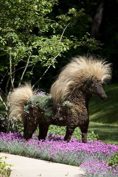 """Topiary Horse planted with and among perennials. For a bit of whimsy and a focal point we have been creating these topiaries made from wire forms stuffed with sphagnum moss. The mane is Nasella and the body is planted with Dianthus """"Tiny Rubies"""" Below and around the horse is Dianthus"""" Fire Witch"""""""