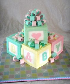 """Pastel Baby Blocks - For a coworker's daughter's baby shower. Four 4"""" square cakes covered in BC and decorated with fondant. Definitely better than my previous baby blocks cake, but still need some work on getting my squares straight. Could have used a better picture too, but it's the only one I have. :-) Thanks for looking!"""