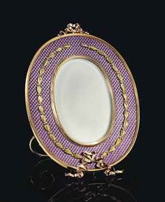 A TWO-COLOUR GOLD-MOUNTED GUILLOCHÉ ENAMEL PHOTOGRAPH FRAME BY FABERGÉ, MOSCOW, 1899-1908. Oval, the body enamelled in translucent mauve over a moiré guilloché ground, centring an oval aperture within a gold reeded mount, applied with a ribbon-tied berried-laurel wreath, surmounted by a rose gold ribbon twist, the mammoth ivory back with gold scroll strut.